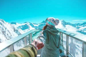man holds the hand of a woman in front of the there is a beautiful snowy mountain