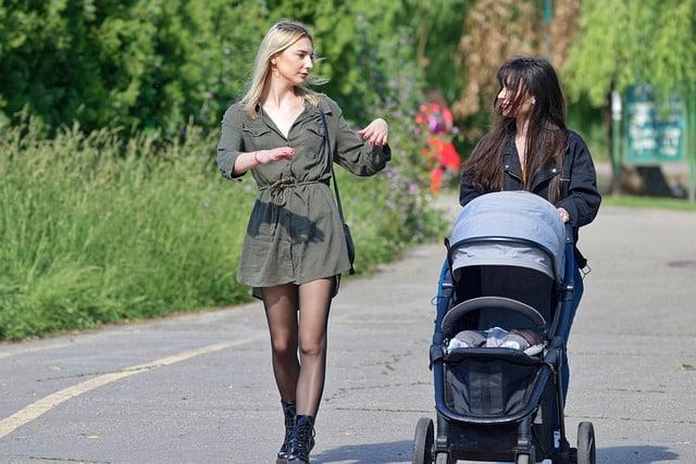 две жени на разходка в парка с бебешка количка